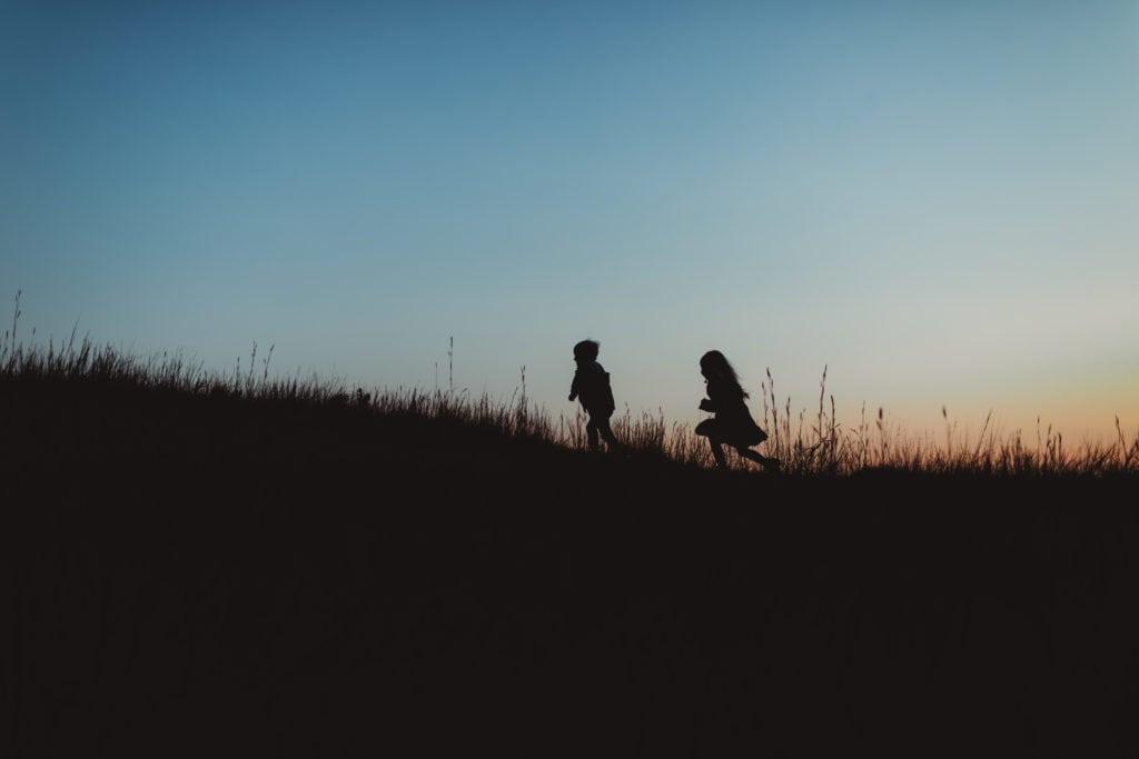 Family Photographer, silhouette of two children running up a grassy hillside at dusk