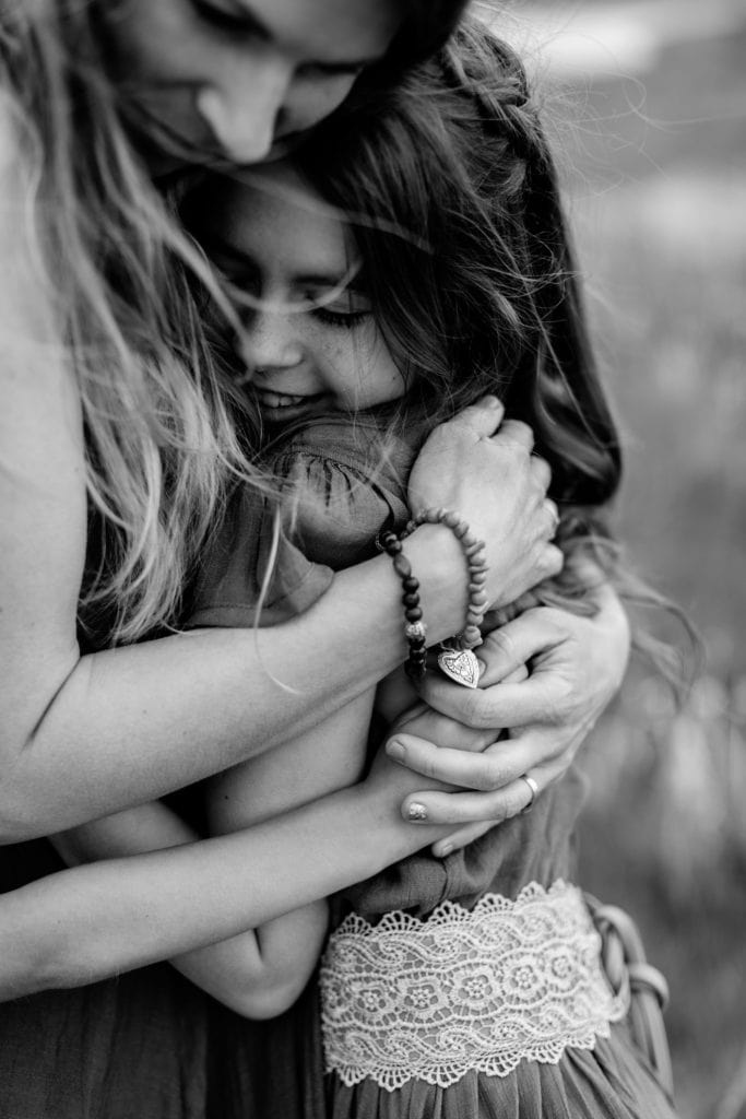 Family Photographer, Mother and daughter embrace tightly, both happy